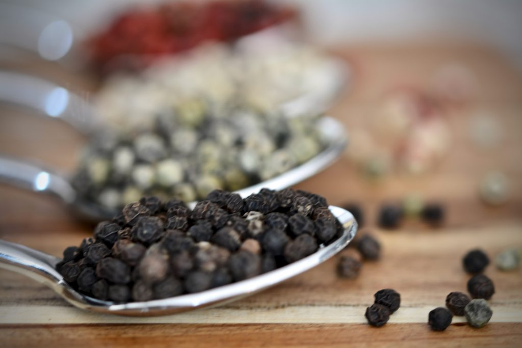 Black, green, white, and red peppercorns on spoons