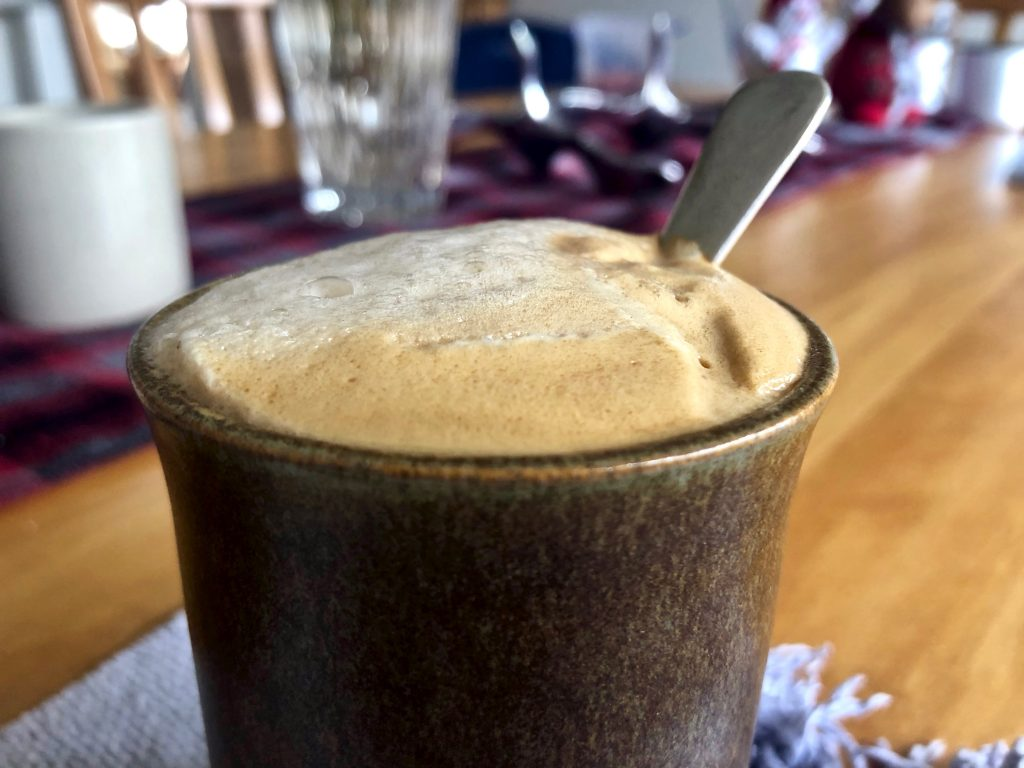 coffee in a cup with a foam head and spoon