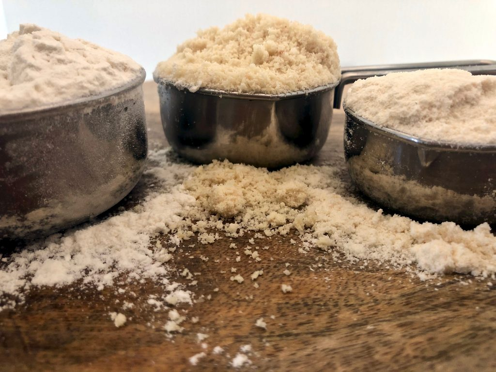 three flours in measuring cups on a board