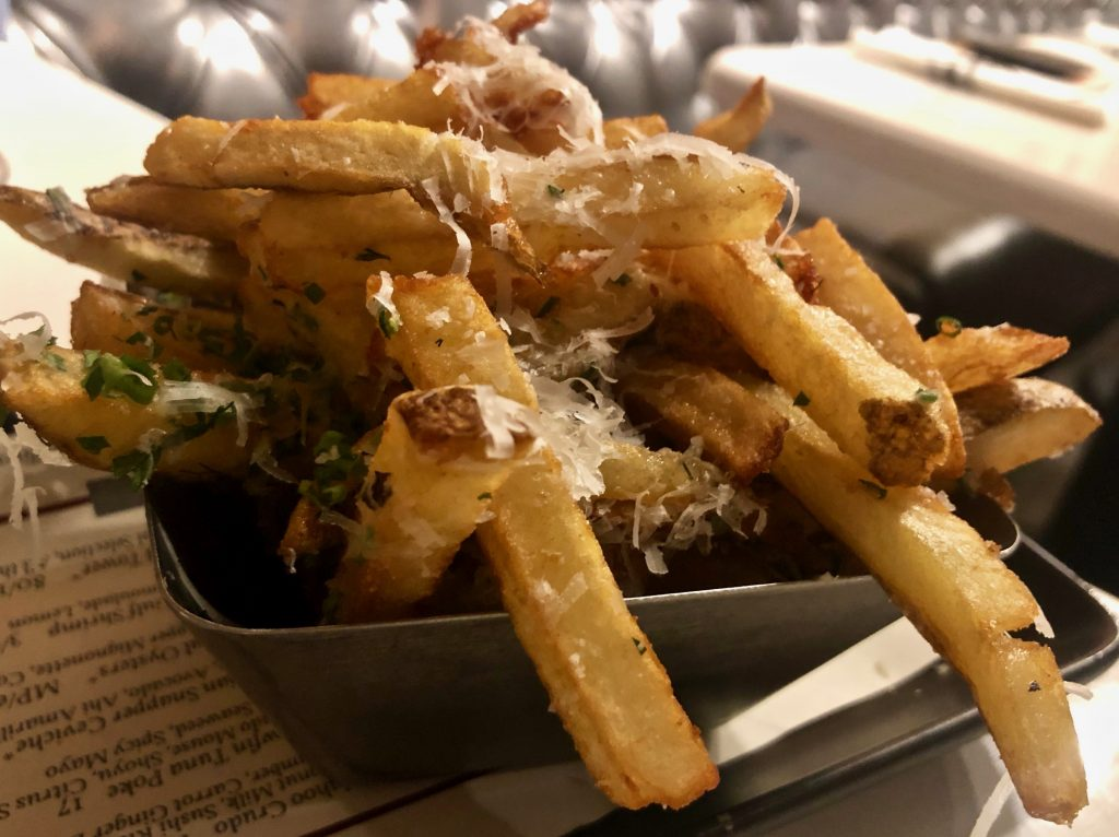 Truffle fries with grated cheese for one served in a bowl on top pf a menu