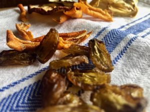 Dehydrated grapes, orange peel and pineapple on a blue and white tea towel