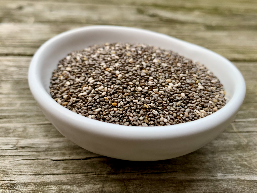 Black and white chia seeds in a white bowl on wood
