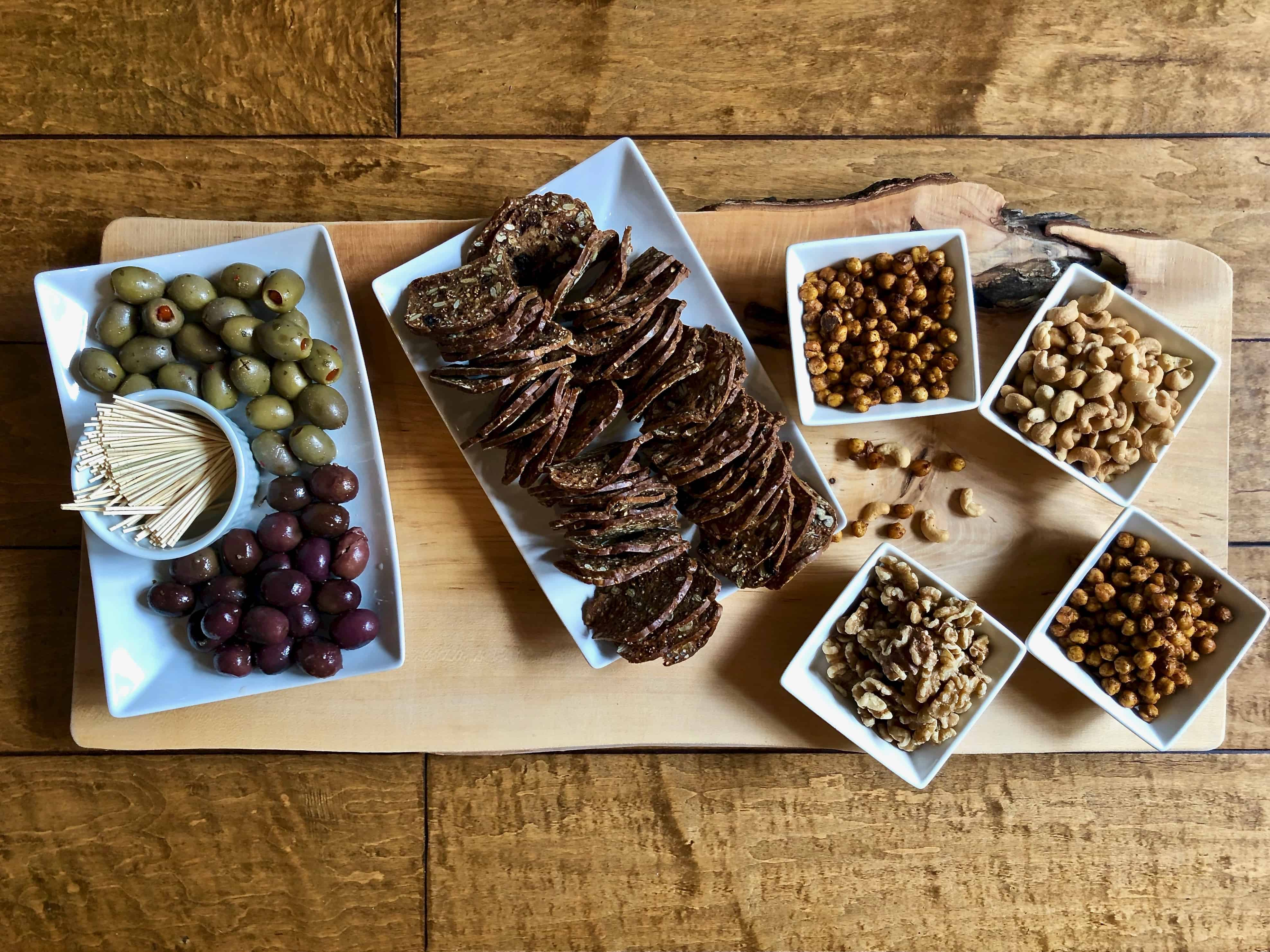 nuts, crackers and olives on a wood board