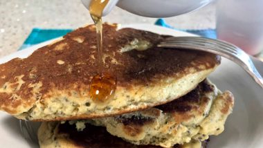 maple syrup running over a stack of pancakes