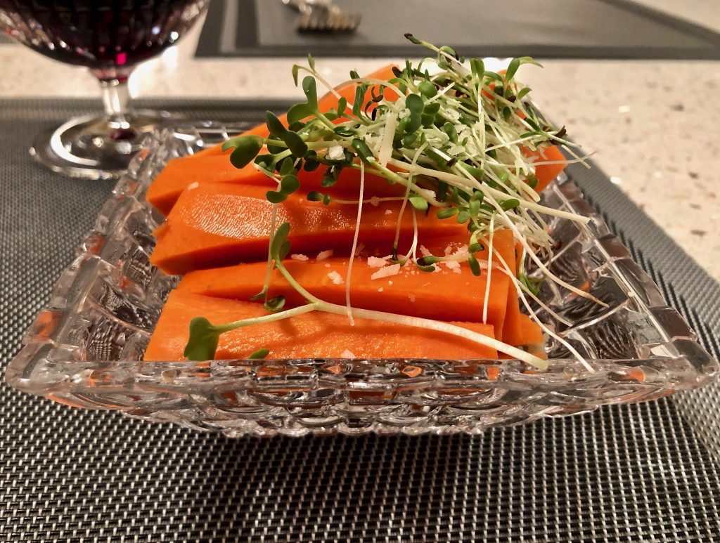 microgreens on top of a sliced carrot salad and glass of red wine