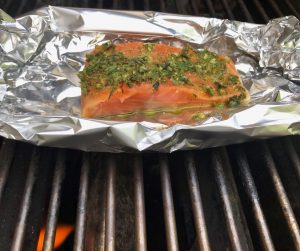 Salmon smothered in pesto on a bbq