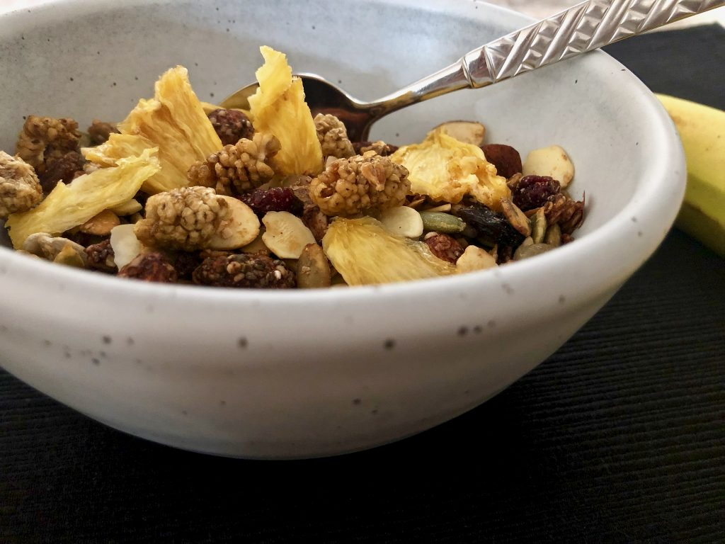 homemade granola with dried fruit in a bowl on a placemat