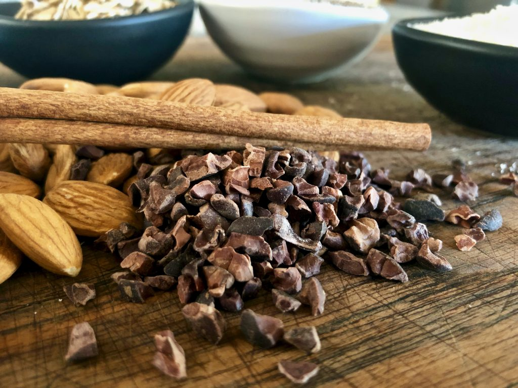 cacao nibs piled with almonds and a cinnamon stick