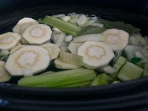 mixed green and white vegetables in the slow cooker with water
