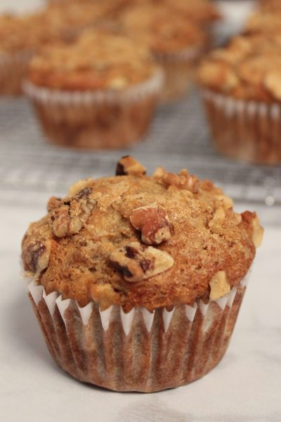 One close up of a banana walnut muffin with others in the background