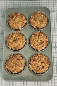 6 banana nut muffins baked in pan on cooling rack