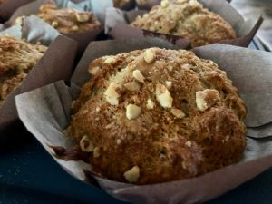 Close up of a baked muffin showing walnuts and brown sugar as the topping