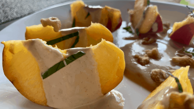 Sliced peaches standing upright smothered in lemon yoghurt sauce and fresh chopped mint