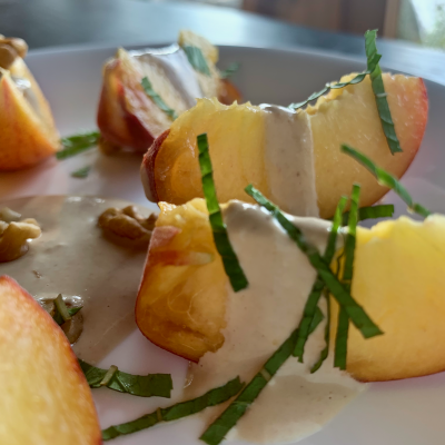 Close up of peach slices on a plate with a creamy, tangy walnut dressing and mint leaves