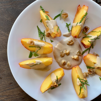 3/4 plate of sliced peaches drizzled with dressing and sliced mint leaves and sprinkled with walnut pieces