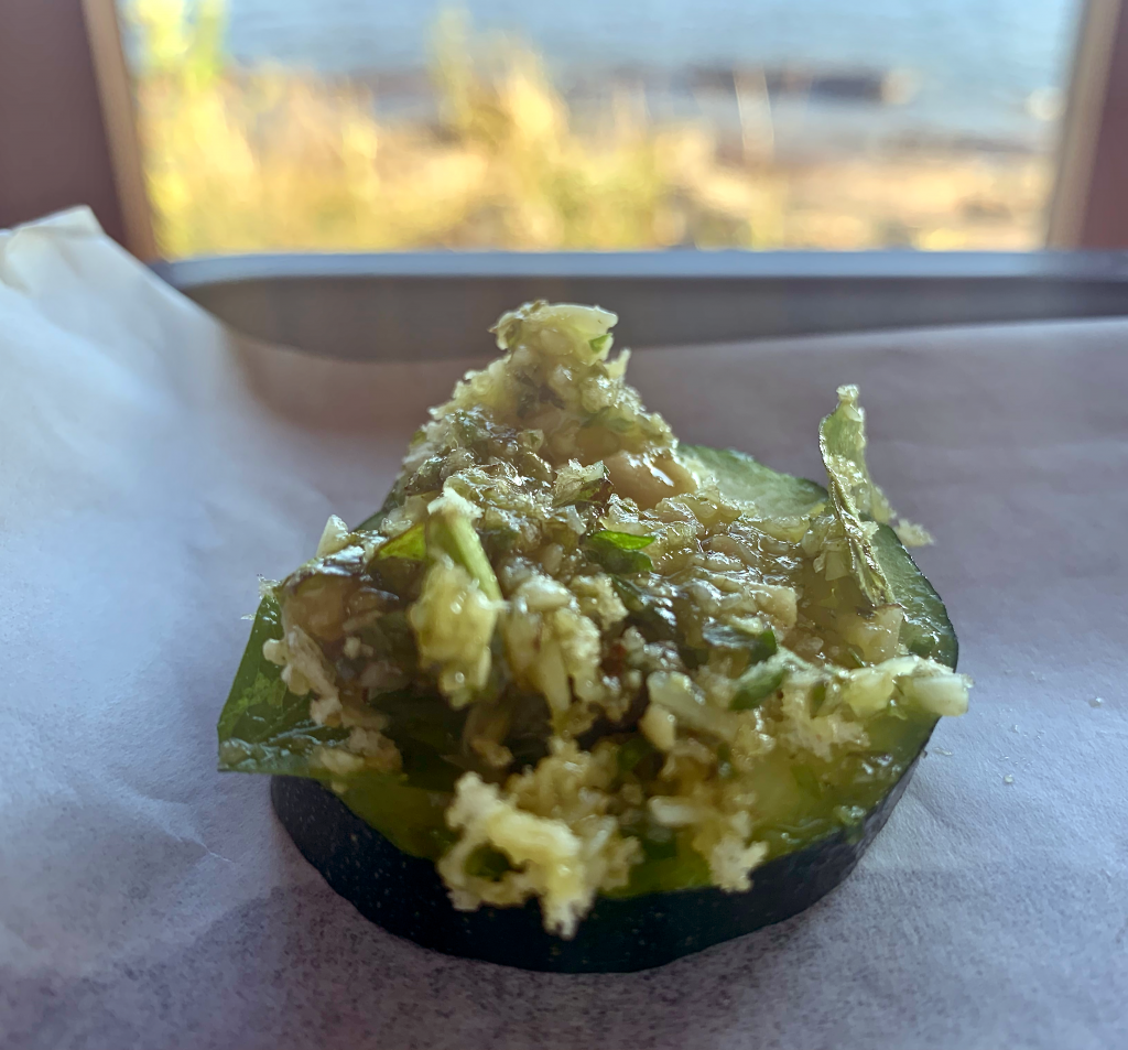 A dollop of pesto on a zucchini slice