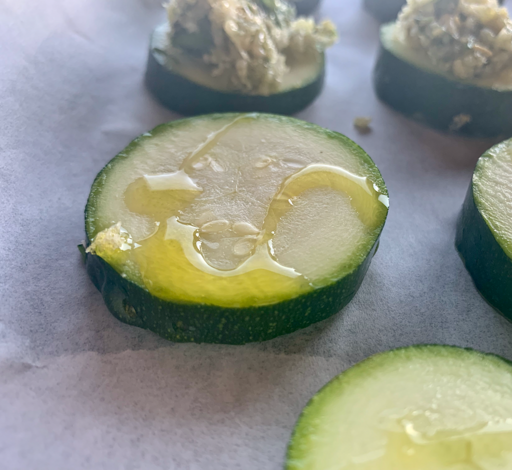 olive oil drizzled over a slice of zucchini