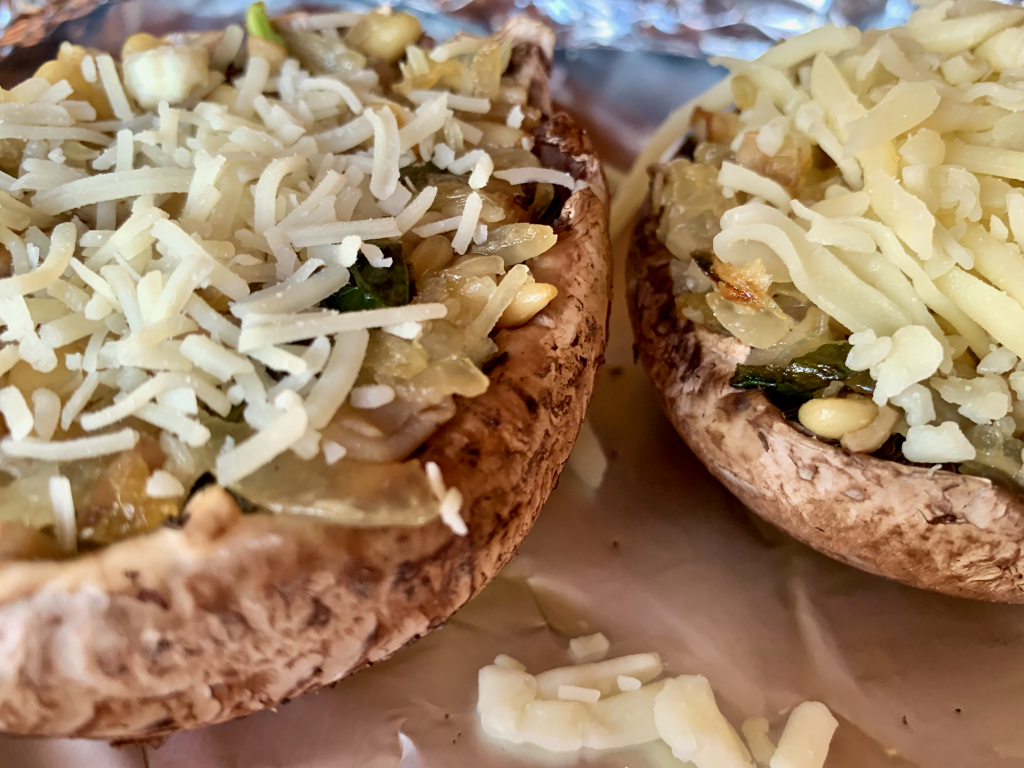 Two mushroom stuffed caps one with cheddar and one with parmesan cheese