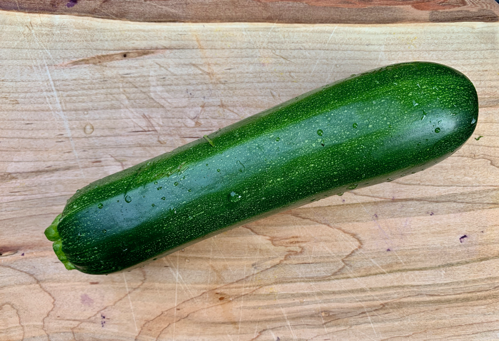 Green zucchini on a wood board