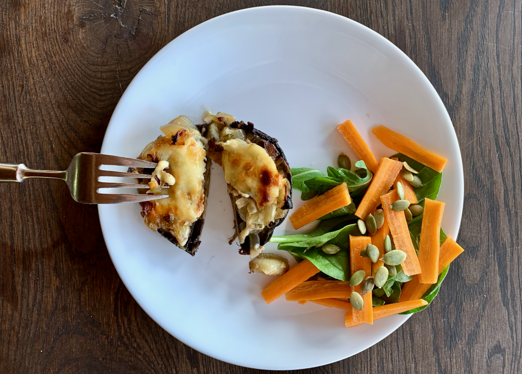 birds eye view of a stuffed mushroom on a plate with salad