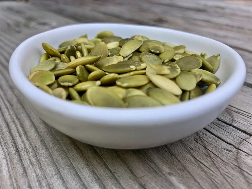 Pepitas or pumkin seeds in a small white bowl on wood