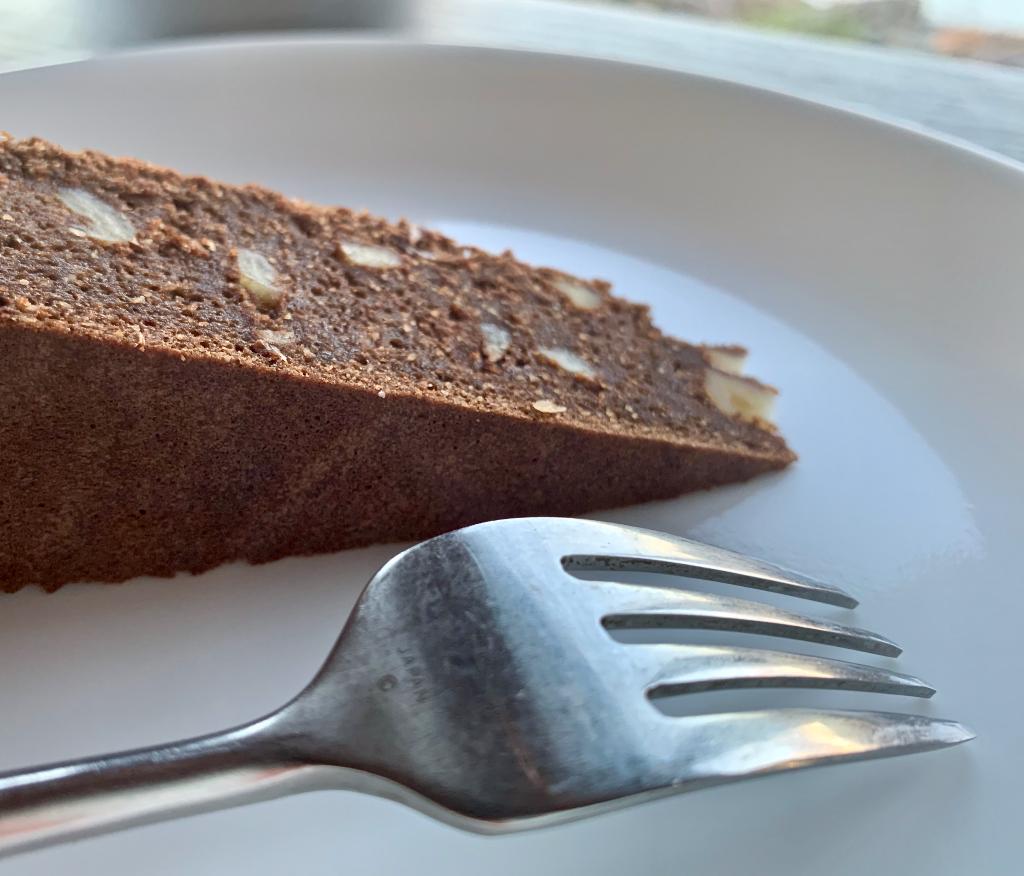 Close up of a slice of chocolate walnut cardamom torte