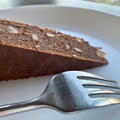 Slice of chocolate walnut torte on a plate with a fork