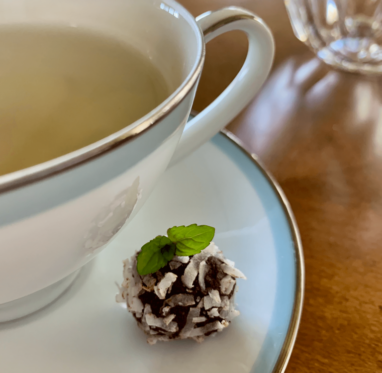 Truffle on a saucer with mint tea in a cup