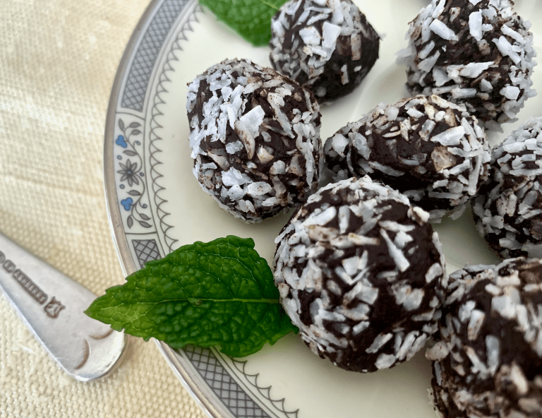 chocolate truffles on a china plate and garnished with fresh mint leaves