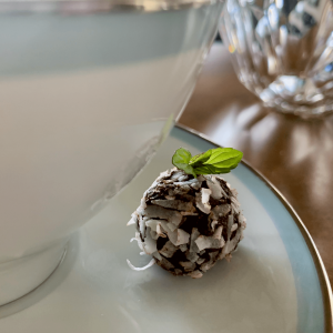 Single mint truffle on a china tea cup with a mint leaf