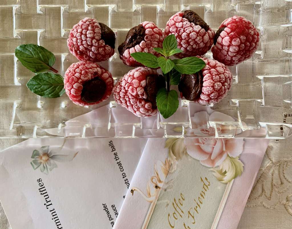 Frozen raspberries stuffed with chocolate truffle on a crystal plate