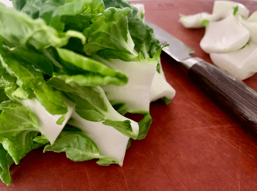 Bok choy leaves separated from the stems on a chopping board with a sharp knife