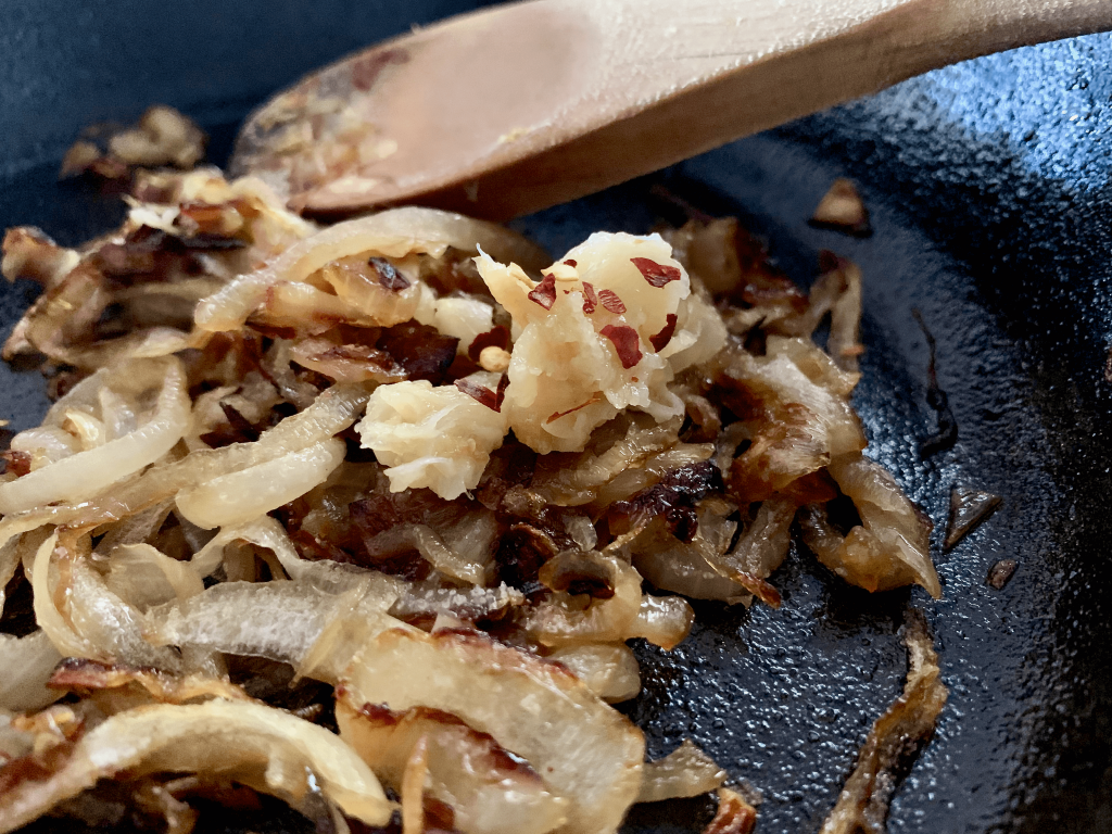 Chilli flakes on onion and garlic in frying pan
