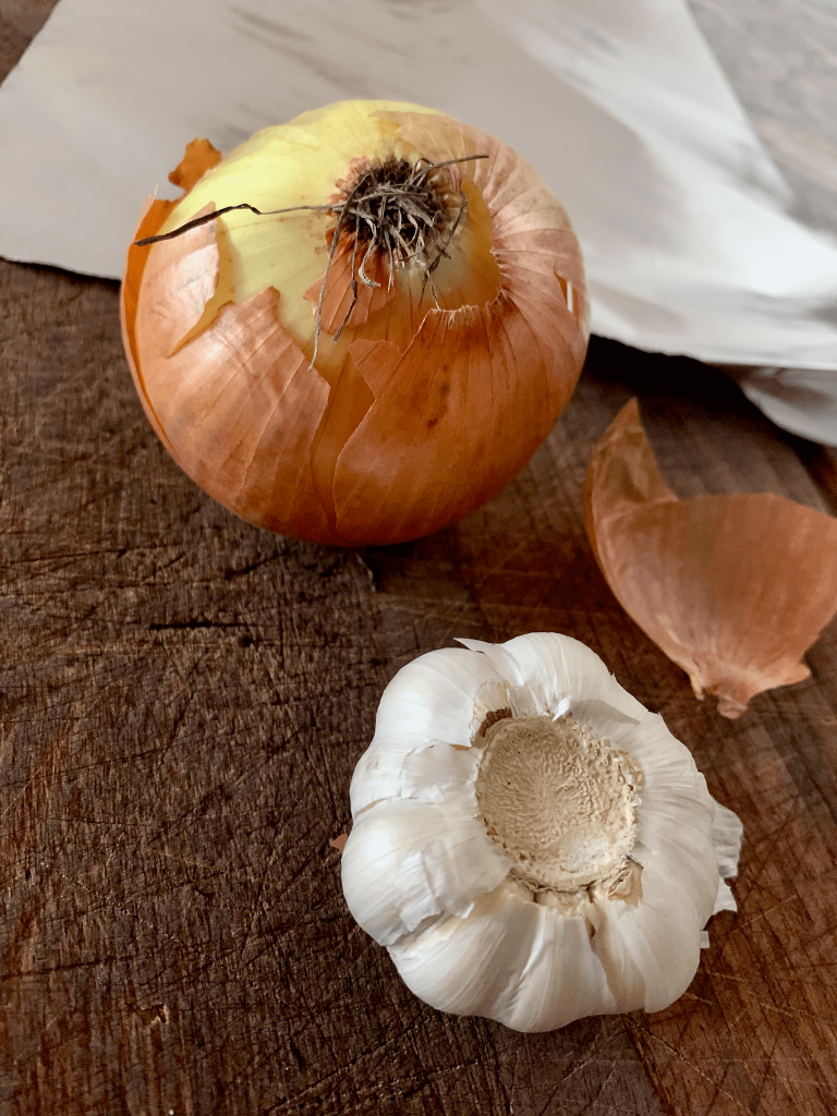 onion and garlic on a chopping board with aluminium foil in the background