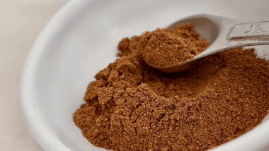DIY Speculaas spice mix on a teaspoon in a white bowl is used in many baking recipes