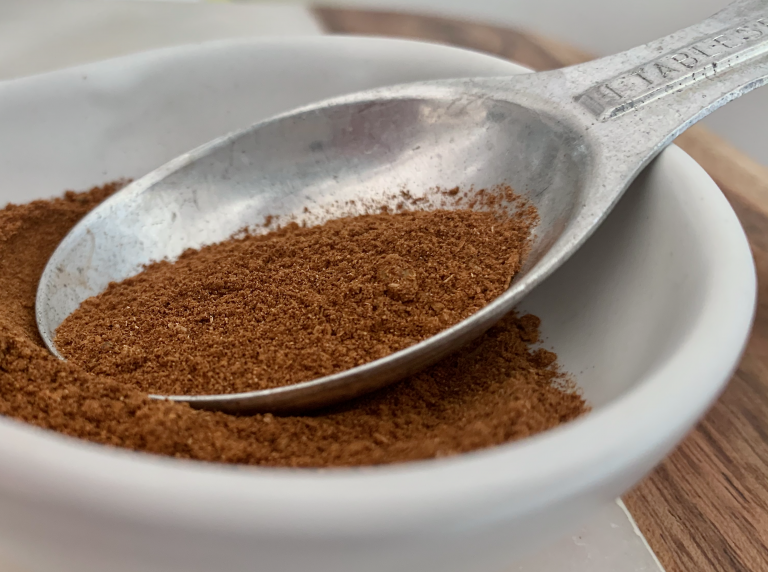 Speculaas spice on a tablespoon in a white bowl