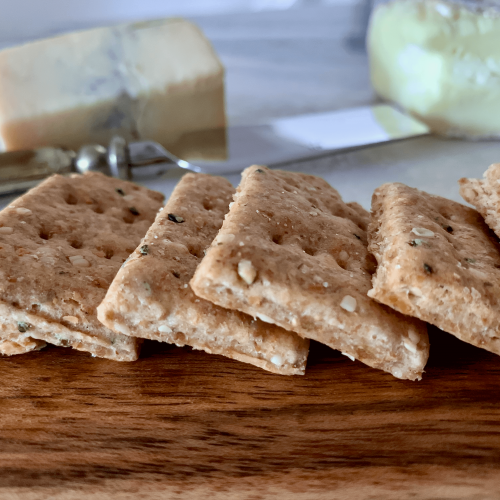 crackers lined up with cheeses and a knife in the background