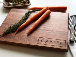 Personalized wood chopping board with carrots and a sharp knife