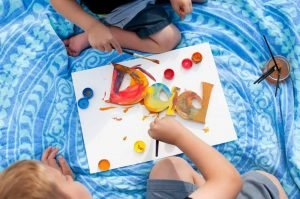 Two kids on a mat painting the wood blocks that spell out 'dad'