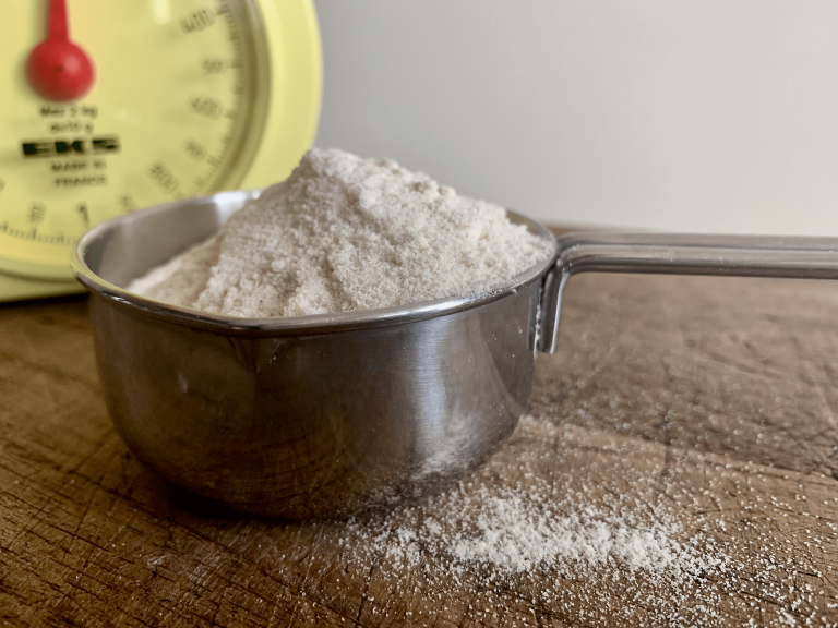 Flour in a measuring cup with a set of yellow scales in the background