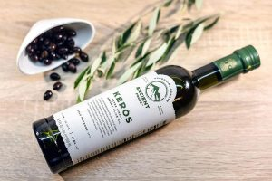 Bottle of olive oil with olives and an olive branch