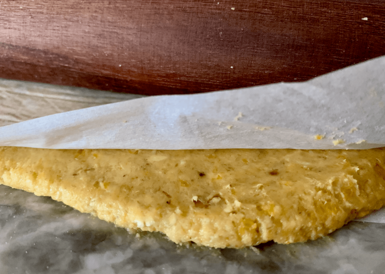 Rolling pin on top of parchment paper which covers the dough