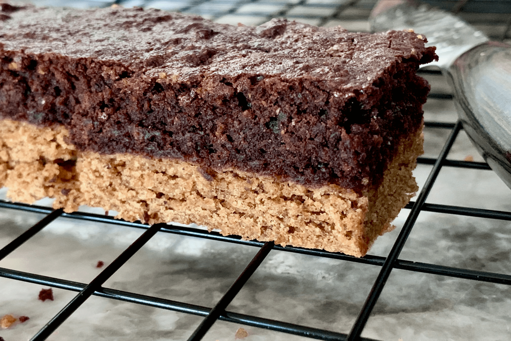 Chocolate almond butter brownie slice cooling on a rack