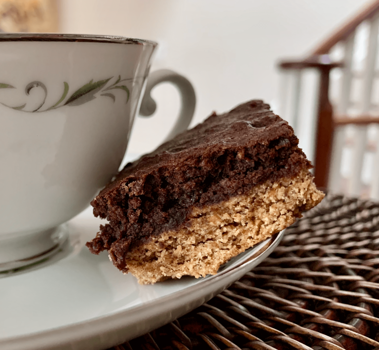 Testing a chocolate almond butter brownie slice with a cup of tea