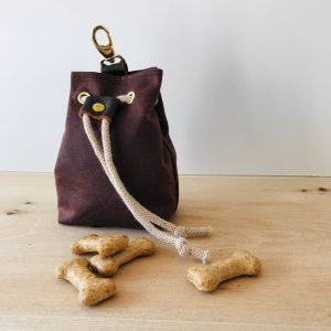Burgundy puppy and dog training treat bag with treats beside it
