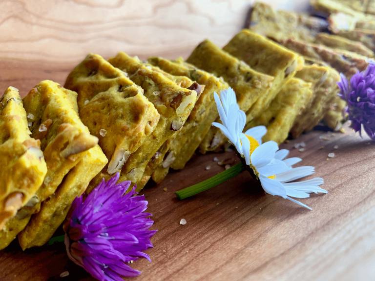 Curry, cheese and pecan crackers on a wood platter with the back end of a daisy