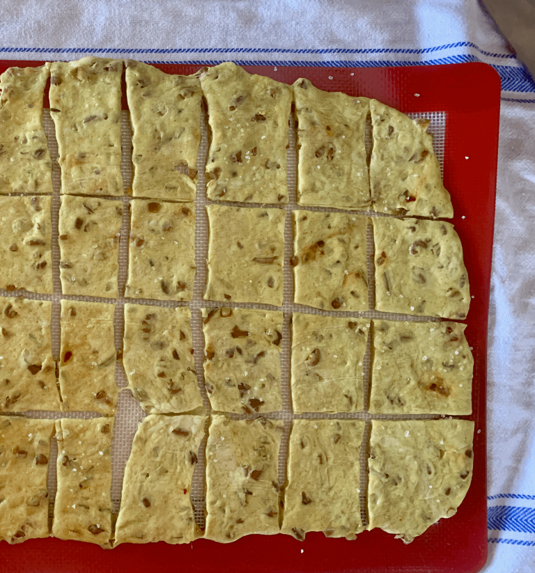 Sourdough crackers rolled out on the baking mat and pre-cut into cracker shapes