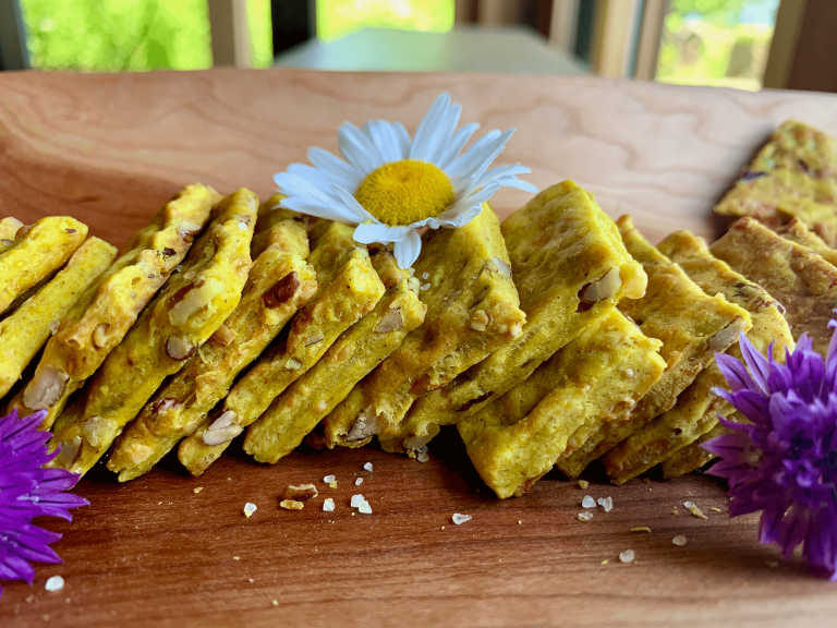 Curried sourdough crackers on a platter with a daisy and chive flowers