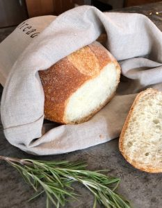 Linen bag with a loaf of bread that doubles as a re-useable kitchen bag