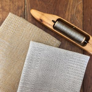 two handwoven linen tea towels with a loom shuttle